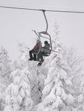 Snowboarder in chair. 2 snowboarders in a chairlift Stock Image
