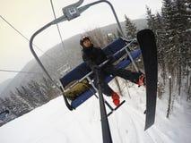 Snowboarder on chairlift. Man snowboarder on chairlift on ski resort Bukovel Stock Photography