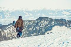 Snowboarder che cammina alla cima stessa di una montagna con lo snowboard in sua mano Fotografia Stock