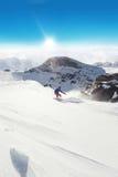 Snowboarder che corre giù sulla pista Immagini Stock