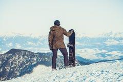 Snowboarder che sta alla cima stessa di uno snowboard della tenuta della montagna con una mano e che gode di bello paesaggio prim Fotografie Stock