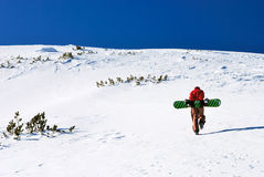 Snowboarder climbing snow slope royalty free stock image