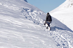 Snowboarder climbing a snowy mountain Royalty Free Stock Image