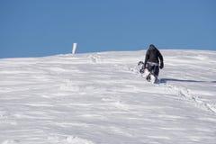 Snowboarder climbing a snowy mountain Royalty Free Stock Photo