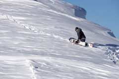 Snowboarder climbing a snowy mountain Stock Photography