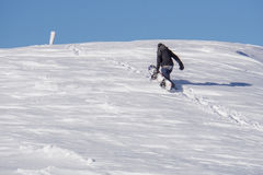 Snowboarder climbing a snowy mountain Royalty Free Stock Images