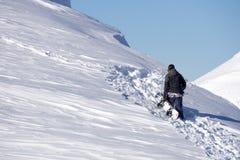 Snowboarder climbing a snowy mountain Stock Photos