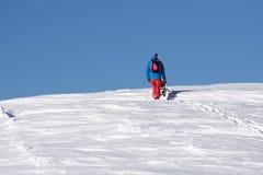 Snowboarder climbing a snowy mountain Royalty Free Stock Photos