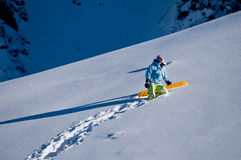 Snowboarder climbing to the peak. Snowboarder climbing through deep snow to reach summit and freeride down the slope Royalty Free Stock Images
