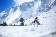 Snowboarder climbing  up the slope Stock Images