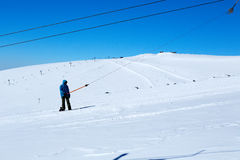 Snowboarder climbs a lift on a mountain against a blue sky Royalty Free Stock Image