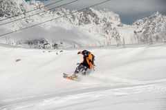 Snowboarder in colorful sportswear riding on the snow hill Royalty Free Stock Images