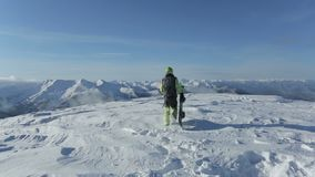 Snowboarder com snowboard que anda na montanha nevado para repicar Snowboarder que aumenta acima no pico de montanha nevado para  video estoque