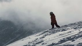 Snowboarder com snowboard que anda na montanha nevado para repicar Snowboarder que aumenta acima no pico de montanha nevado para  vídeos de arquivo