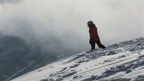 Snowboarder con la snowboard que camina en la montaña nevosa para enarbolar Snowboarder que sube para arriba en el pico de montañ almacen de metraje de vídeo