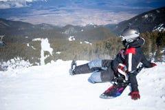 Snowboarder contro le montagne panoramiche di inverno Fotografia Stock