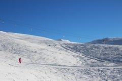 Snowboarder cuesta abajo en cuesta del esquí en la mañana fría del sol Fotografía de archivo libre de regalías