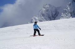 Snowboarder cuesta abajo en cuesta nevosa del esquí en alta montaña Imagen de archivo libre de regalías