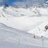 Snowboarder cuesta abajo en rastro y las montañas del freeride en nubes Foto de archivo