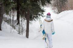 Snowboarder da moça que vai para baixo em uma montanha nevado na floresta Imagens de Stock