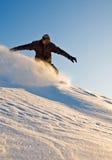 Snowboarder de alta velocidad en la puesta del sol Foto de archivo