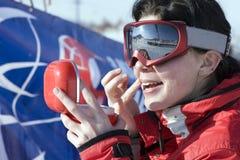 Snowboarder de la muchacha del deporte que aplica el paquete de cara al aire libre Foto de archivo libre de regalías