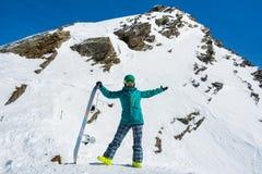 Snowboarder de la muchacha en el fondo de las altas montañas coronadas de nieve en s Fotografía de archivo libre de regalías