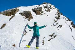 Snowboarder de la muchacha en el fondo de las altas montañas coronadas de nieve en s Fotografía de archivo