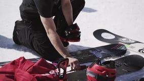 Snowboarder in de laarzen van de overhemdsmoeilijke situatie op snowboard Het van brandstof voorzien van de benzinepomp encamp Zo stock video