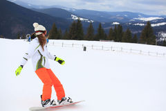Snowboarder de sexo femenino en una cuesta de montaña Imágenes de archivo libres de regalías