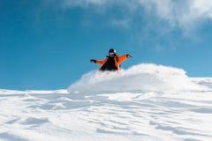 Snowboarder de sexo masculino en la ropa de deportes anaranjada brillante que monta abajo de la colina de la nieve del polvo Fotos de archivo libres de regalías