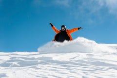 Snowboarder de sexo masculino en la ropa de deportes anaranjada que monta abajo de la colina de la nieve del polvo Imagen de archivo libre de regalías
