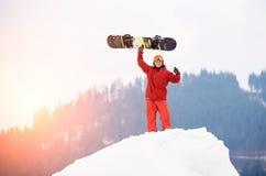 Snowboarder de sexo masculino joven que se coloca en el top de la colina nevosa con, llevando a cabo la cabeza antedicha disponib Fotografía de archivo libre de regalías