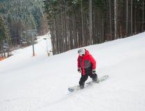 Snowboarder de sexo masculino que monta abajo de la montaña en día de invierno Imagen de archivo libre de regalías