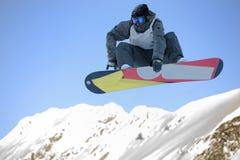 Snowboarder de sexo masculino que salta con el snowboard Foto de archivo