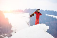 Snowboarder de sexo masculino que se coloca en el top de la colina nevosa, sosteniendo la snowboard disponible, mostrando los pul Imagen de archivo