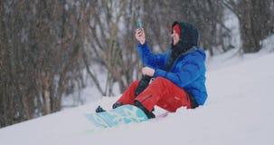 Snowboarder de sexo masculino que se sienta en la nieve que toma las fotos en el paisaje hermoso del teléfono del centro turíst metrajes