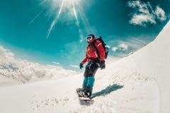 Snowboarder del hombre freeriding en la cuesta fuera de pista del esquí Imagen de archivo