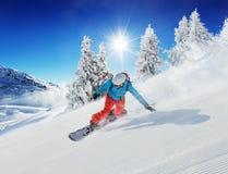 Snowboarder del hombre joven que corre abajo de la cuesta en montañas alpinas Imágenes de archivo libres de regalías