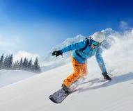 Snowboarder del hombre joven que corre abajo de la cuesta en montañas alpinas foto de archivo