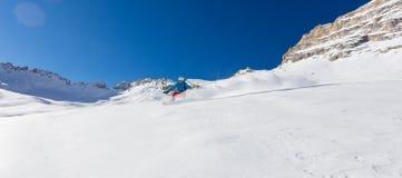 Snowboarder del hombre joven que corre cuesta abajo en la nieve del polvo, MES alpino Imagenes de archivo
