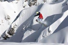 Snowboarder del vuelo en las montañas Imágenes de archivo libres de regalías