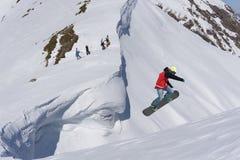 Snowboarder del vuelo en las montañas Fotos de archivo libres de regalías