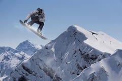 Snowboarder del vuelo en las montañas Fotografía de archivo libre de regalías