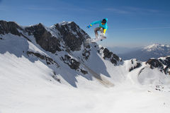 Snowboarder del vuelo en las montañas Imagen de archivo
