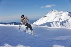 Snowboarder del vuelo en las montañas Imagenes de archivo