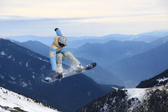 Snowboarder del vuelo en las montañas Foto de archivo