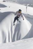 Snowboarder del vuelo en las montañas Imagen de archivo libre de regalías