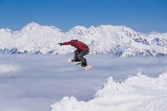 Snowboarder del vuelo en las montañas Fotografía de archivo