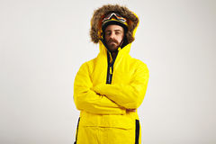 Snowboarder demonstrating bright anorak coat. Attractive young man wearing snowboard helmet and goggles and a bright yellow anorak with arms crossed on white Stock Images